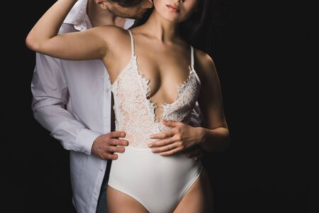Foto de Cropped view of young man in white shirt kissing and hugging sexy Asian girlfriend in white lingerie isolated on black background - Imagen libre de derechos