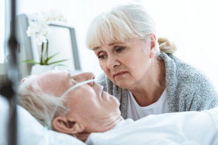 Foto de sad senior woman looking at husband in coma in clinic - Imagen libre de derechos