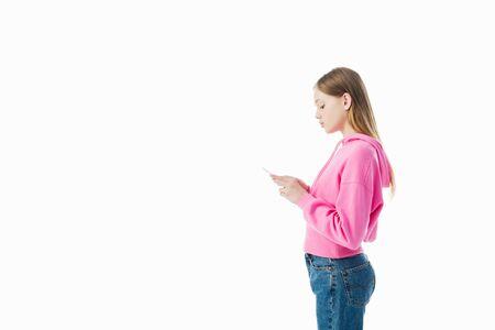 Foto de side view of teenage girl in pink hoodie using smartphone isolated on white - Imagen libre de derechos