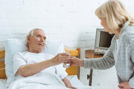 Foto de senior woman giving glass of water to sick husband in hospital - Imagen libre de derechos