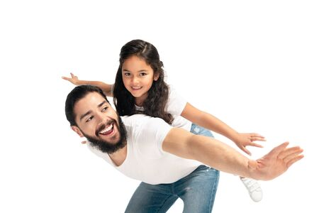 Foto de happy latin father carrying on back cute daughter with outstretched hands isolated on white - Imagen libre de derechos