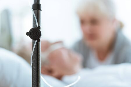 Foto de selective focus of sad senior woman with husband in coma in clinic - Imagen libre de derechos