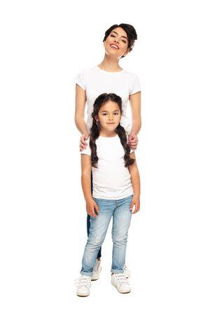 Foto de happy latin mother standing with cute daughter isolated on white - Imagen libre de derechos