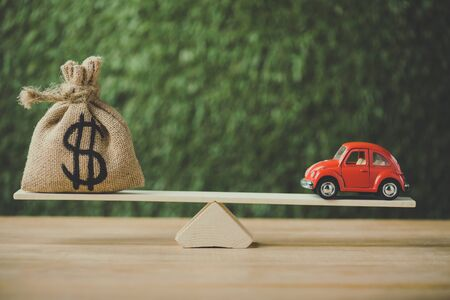 Foto de toy car and money bag with dollar sign balancing on seesaw on green background - Imagen libre de derechos
