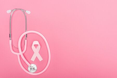 Foto de top view of pink stethoscope and breast cancer symbol on pink background with copy space - Imagen libre de derechos