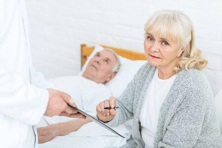 Foto de cropped view of doctor with clipboard, senior woman and ill patient - Imagen libre de derechos