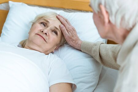 Foto de partial view of senior sick woman with husband in clinic - Imagen libre de derechos