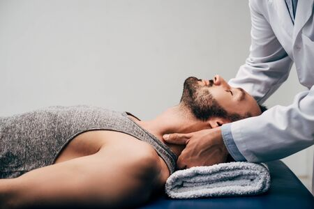 Photo pour Chiropractor massaging neck of handsome man lying on Massage Table on grey background - image libre de droit