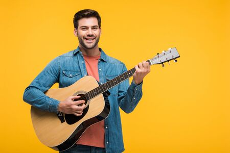 Photo for Handsome smiling man playing acoustic guitar isolated on yellow background - Royalty Free Image