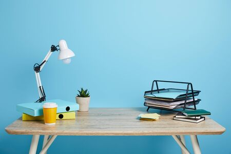 Foto de Workplace with papers, succulent and coffee in plastic cup on wooden table on blue background - Imagen libre de derechos