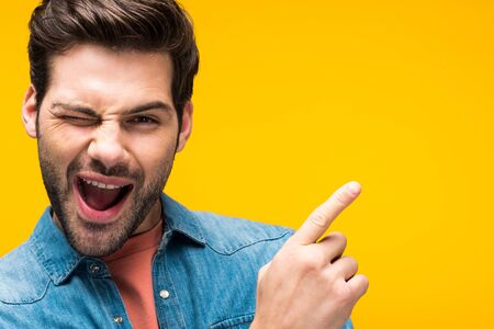 Photo pour Handsome man pointing with finger and winking isolated on yellow background - image libre de droit