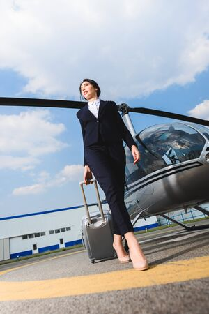Photo pour Low angle view of businesswoman in formal wear with suitcase near helicopter - image libre de droit
