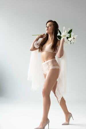 Photo pour Tender young woman in beige lingerie and mesh sleeves walking with white lilies - image libre de droit