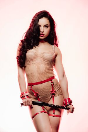 Photo for Sexy brunette young woman in red swordbelt, collar and handcuffs holding flogging whip on light background - Royalty Free Image