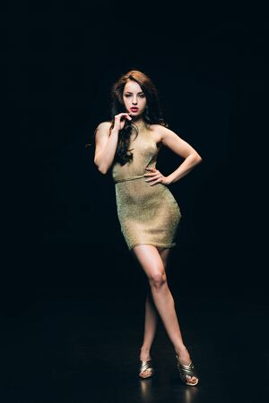 Photo for Sexy elegant young woman in golden transparent dress posing isolated on black background - Royalty Free Image