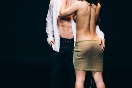 Foto de Back view of naked woman with sexy buttocks standing near elegant boyfriend with bare torso isolated on black background - Imagen libre de derechos