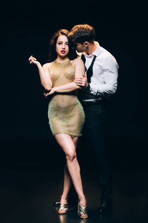 Photo for Elegant young man kissing hot young girl in transparent dress isolated on black background - Royalty Free Image