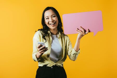 Photo for Happy Asian girl using smartphone and holding pink speech bubble, isolated on yellow background - Royalty Free Image