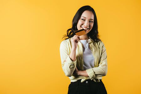 Photo pour Cheerful Asian woman holding credit card, isolated on yellow background - image libre de droit