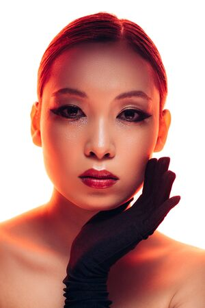 Photo for Beautiful Asian girl in black gloves with makeup in red light, isolated on white background - Royalty Free Image