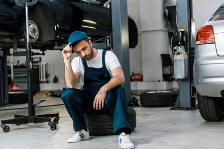 Photo for Upset bearded man touching cap and sitting on car tire - Royalty Free Image