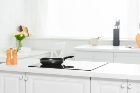 Photo pour modern kitchen with white counter, cooker and frying pan - image libre de droit