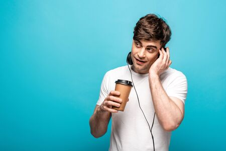 Photo pour cheerful young man in headphones holding coffee to go and looking away on blue background - image libre de droit