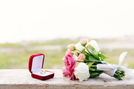 Photo for wedding ring in red box and bouquet on wooden surface - Royalty Free Image