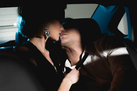 Photo pour sensual man and young woman kissing in back seat of car in dark - image libre de droit