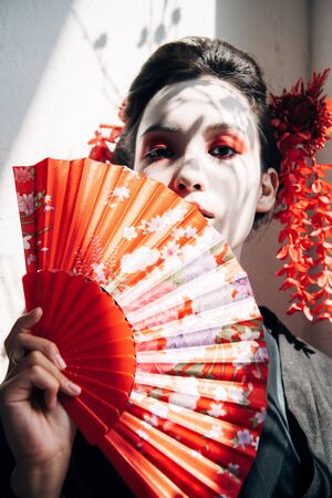 Photo pour portrait of beautiful geisha with red and white makeup holding hand fan in sunlight - image libre de droit