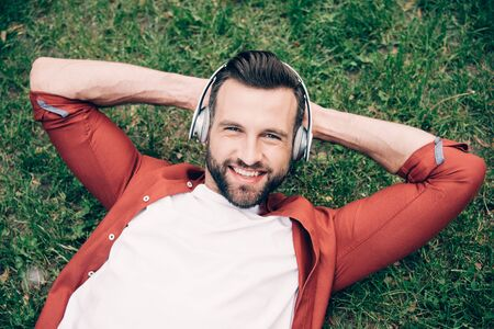 Photo for young man lying on grass with hands behind head, listening to music, smiling and looking at camera - Royalty Free Image