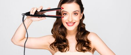 Photo for happy beautiful brunette woman with curls and makeup holding straightening flat iron isolated on grey, panoramic shot - Royalty Free Image