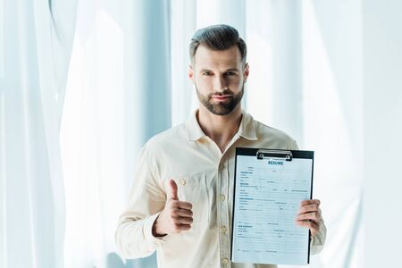 Photo for handsome bearded man showing thumb up and holding clipboard with resume letters - Royalty Free Image