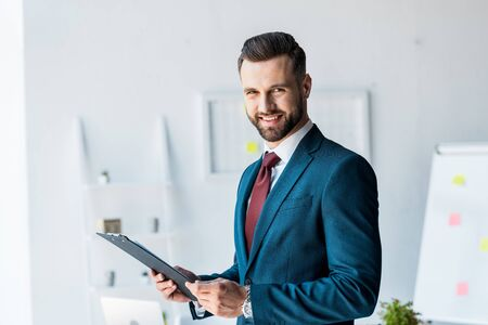 Photo pour cheerful bearded man in suit holding clipboard in office - image libre de droit