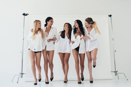 Photo pour full length view of five sexy multiethnic girls wearing white shirts and heels smiling on grey - image libre de droit