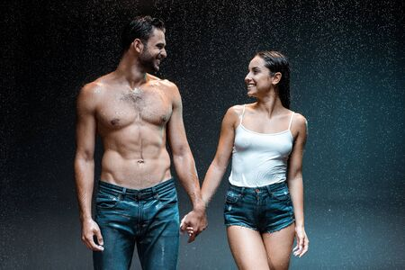 Photo pour happy shirtless man holding hands with wet girl in denim shorts on black - image libre de droit
