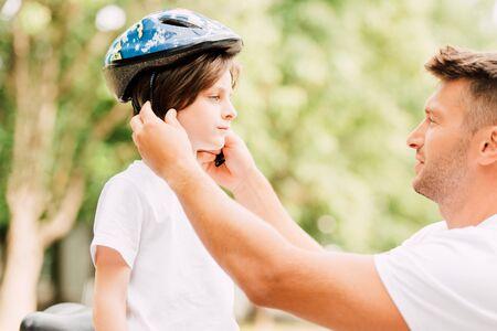 Foto de side view of father putting helmet on son while boy looking at dad - Imagen libre de derechos
