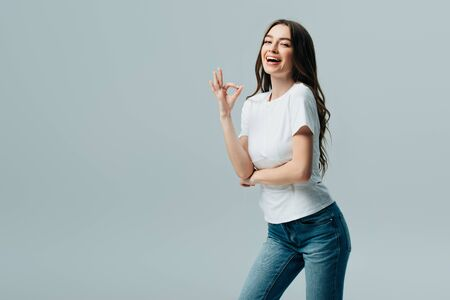 Photo for beautiful girl in white t-shirt showing ok sign isolated on grey - Royalty Free Image