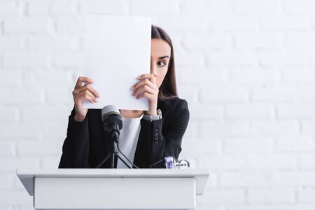 Photo pour young lecturer suffering from fear of public speaking hiding face with paper sheet while standing on podium tribune - image libre de droit