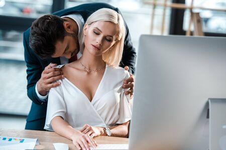 Photo pour selective focus of bearded businessman flirting with woman sitting near table - image libre de droit
