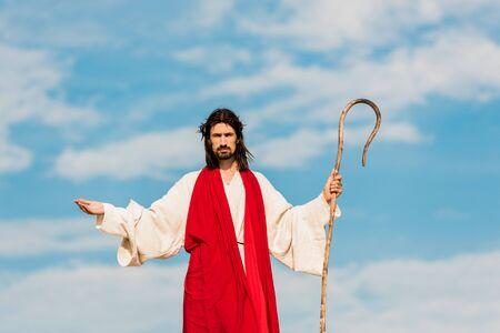 Foto de handsome man in wreath with outstretched hands holding cane - Imagen libre de derechos