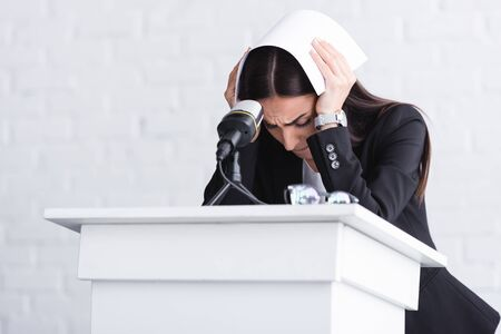 Foto de young lecturer, suffering from fear of public speaking, standing on podium tribune and covering head with paper - Imagen libre de derechos