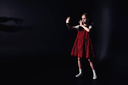 Photo pour scared child standing in darkness with outstretched hands on black background - image libre de droit