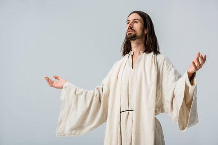 Foto de man in jesus robe with outstretched hands isolated on grey - Imagen libre de derechos