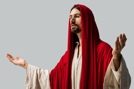 Foto de handsome bearded man in red hood with outstretched hands isolated on grey - Imagen libre de derechos