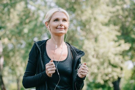 Photo pour beautiful mature sportswoman looking away while running in park and listening music in earphones - image libre de droit