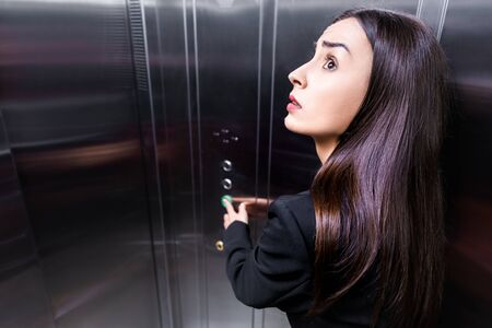 Foto de scared businesswoman, suffering from claustrophobia, looking up while pushing button in elevator - Imagen libre de derechos