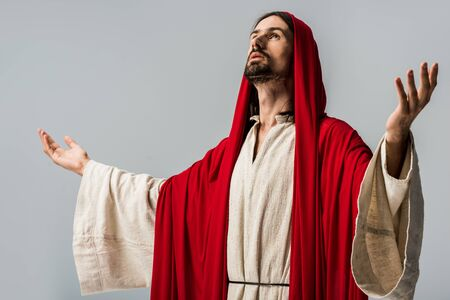 Foto de bearded man in red hood praying with outstretched hands isolated on grey - Imagen libre de derechos