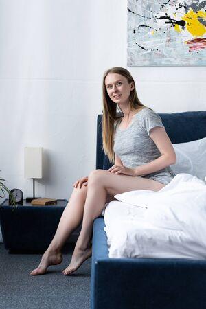 Foto de happy young woman in bed looking at camera in morning - Imagen libre de derechos