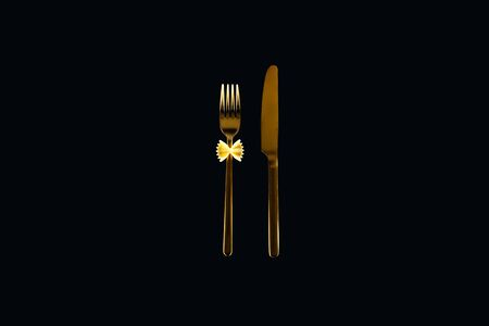 Photo pour uncooked farfalle pasta on metal fork near knife isolated on black - image libre de droit